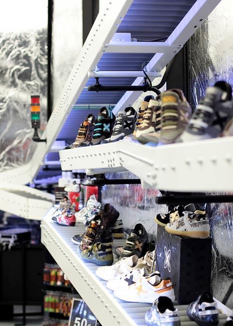 Buty są wystawione na kojarzących się z fabryką przenośnikach taśmowych. fot. ARC