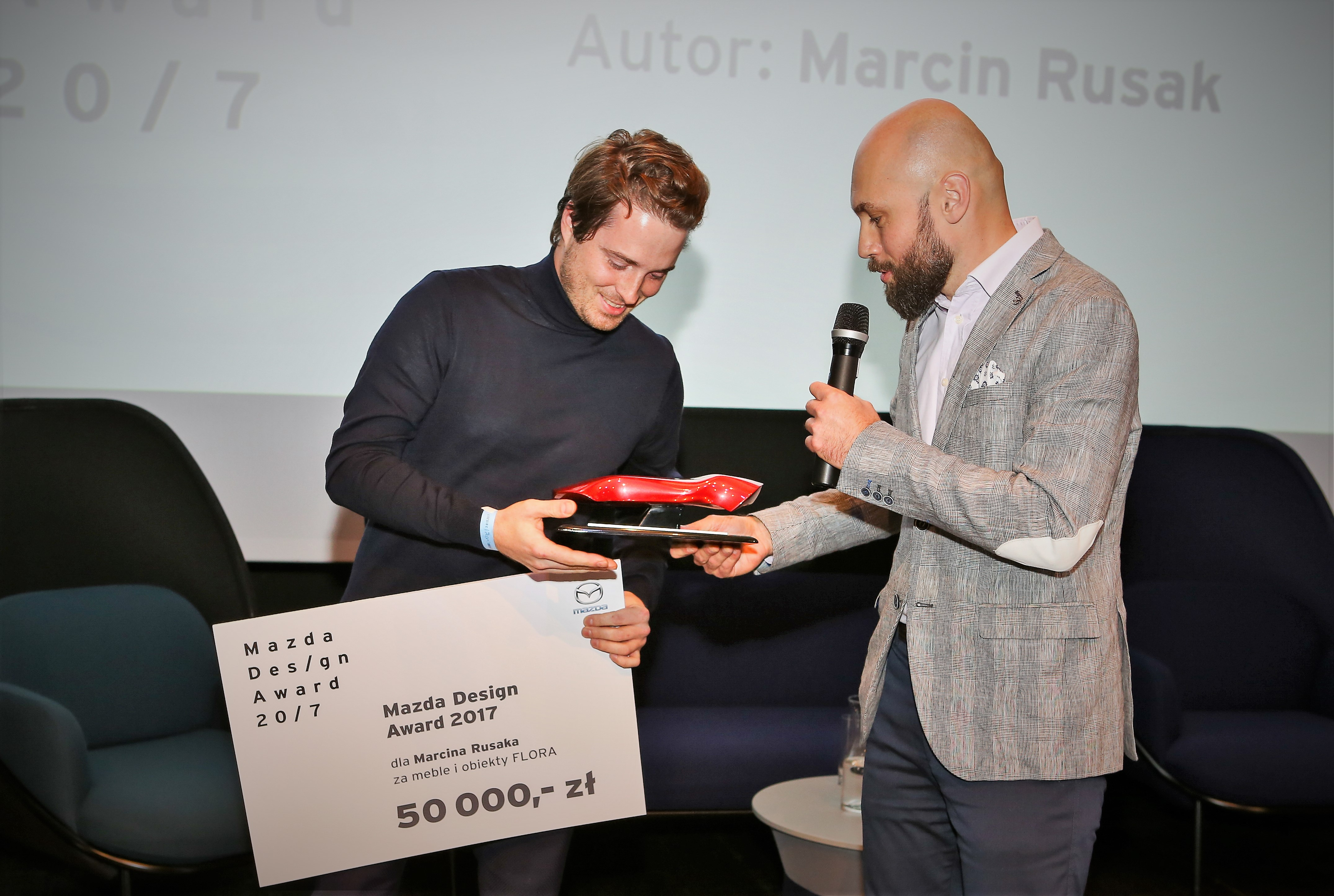 Marcin Rusak odbiera nagrodę z rąk Szymona Sołtysika.